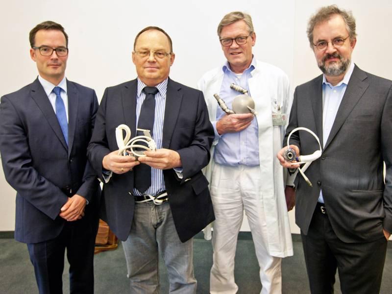 Vier Männer, drei davon halten medizinische Geräte in den Händen.