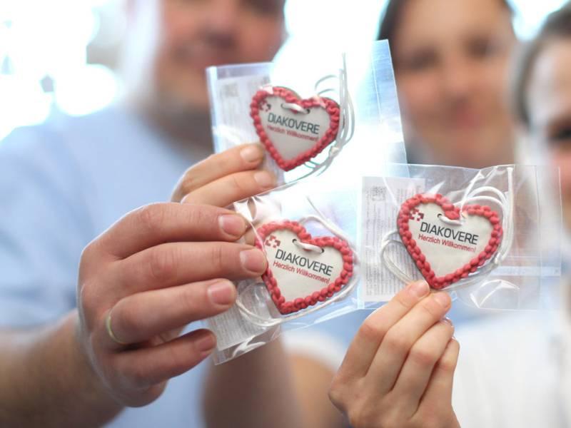 """Drei Menschen halten drei in Plastik eingepackte Herzen mit der Aufschrift """"Diakovere"""" in den Händen."""