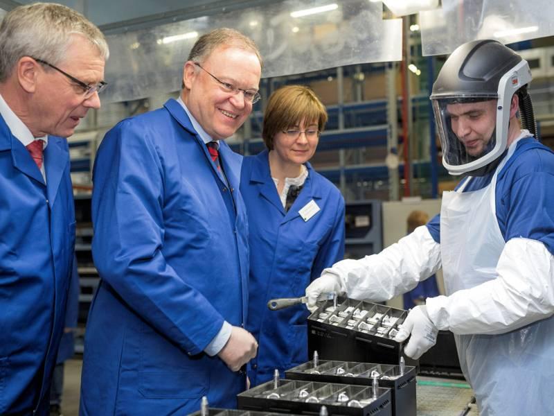 Eine Frau und drei Männer in Industrieanlage.