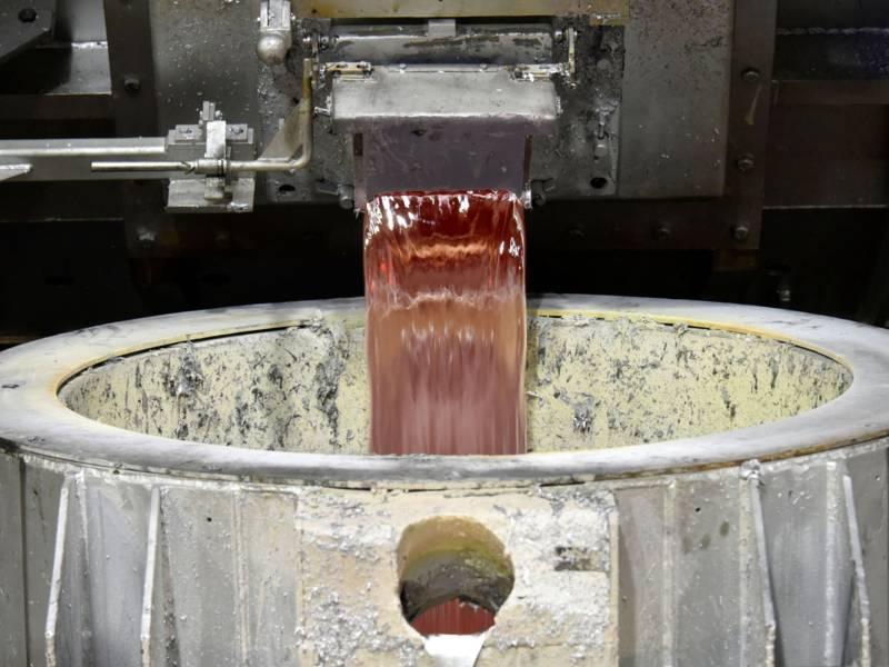 Flüssiges Metall fließt durch einen Augussöffnung aus einem Behälter in eine Auffangvorrichtung.