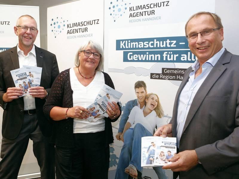 """Eine Frau und zwei Määner halten Flyer vor Plakat mit der Aufschrift """"Klimaschutz - Gewinn für alle"""""""