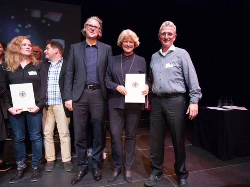 Drei Personen posieren mit einer Urkunde.