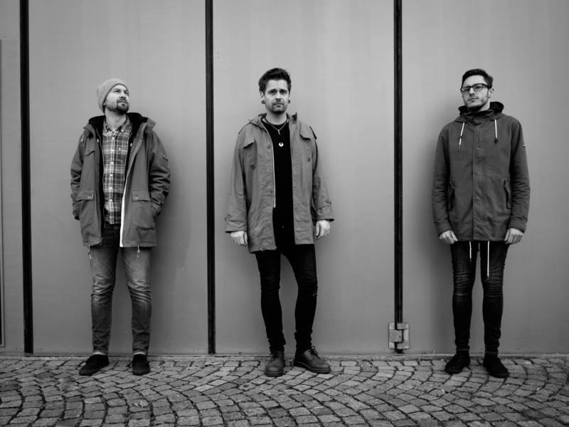 Drei Männer stehend an einer grauen Wand.