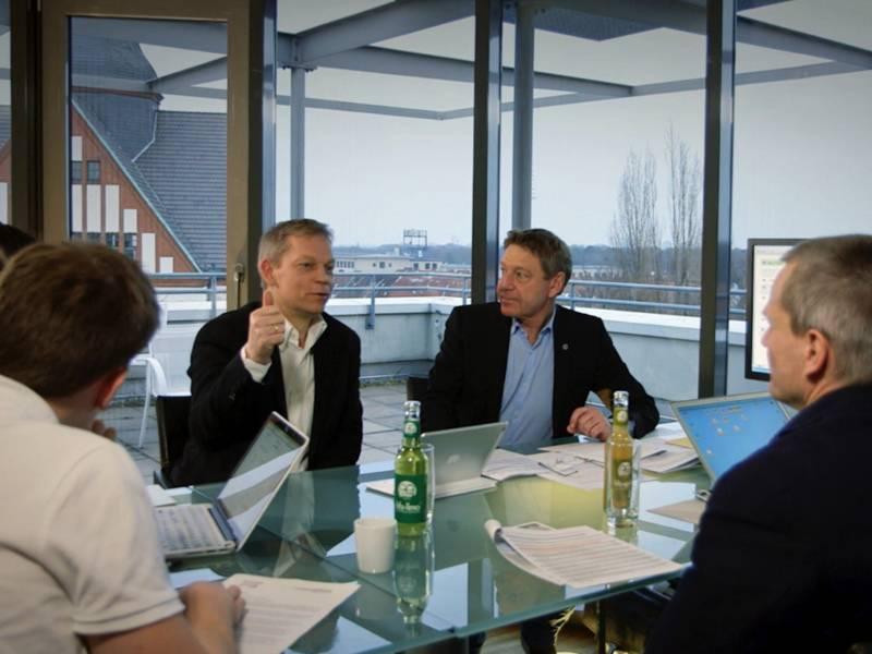 Vier Männer sitzen mit Arbeitspapieren und Laptops an einen Tisch