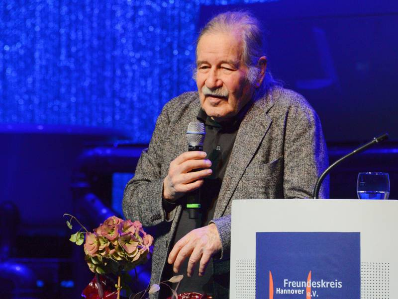 Ein Mann mit Mikrofon in der Hand steht neben einem Rednerpult.