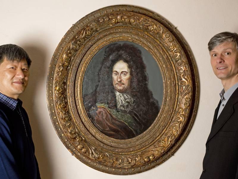Zwei Männer stehen vor einem Portrait von Leibniz.