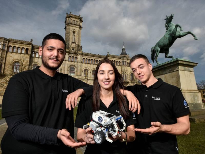 Eine Frau und zwei Männer vor historischem Gebäude halten eine kleine Maschine in den Händen.