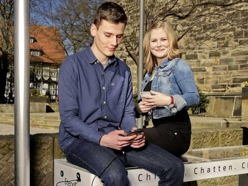 Ein Mann und eine Frau sitzen auf einer Parkbank und haben Smartphones in den Händen.