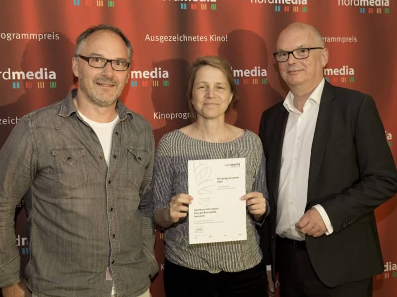 Zwei Männer und eine Frau halten eine Urkunde