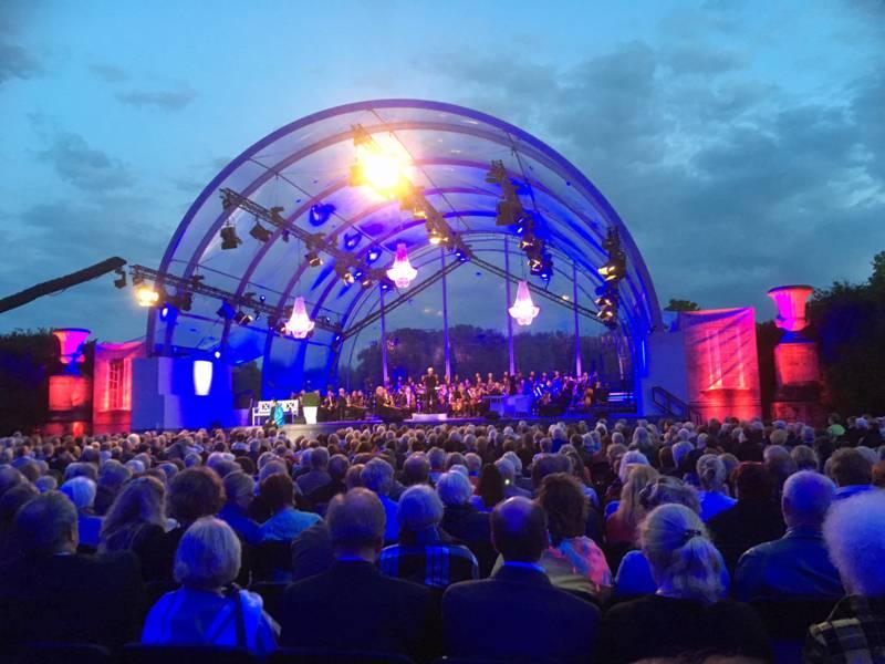 Zuschauer sitzen in Stuhreihen vor einer Open-Air-Bühne
