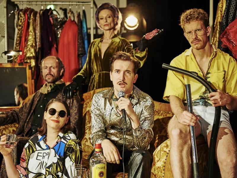 Ein Mann im goldenen Hemd singt in ein Mikrofon, um ihn herum mehrere Personen in schrillen Klamotten.