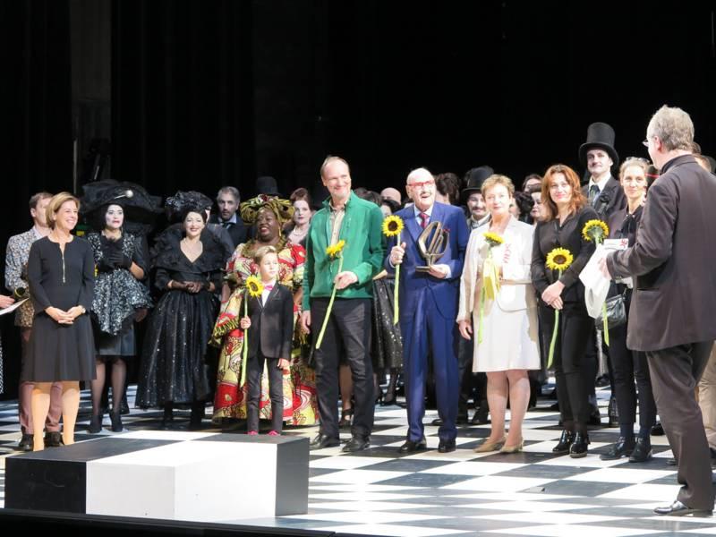 Schauspieler und Schauspielerinnen, der Regisseur und die Kostümbildnerin erhalten auf der Bühne des Opernhauses den Wanderpreis und gelbe Sonnenblumen.
