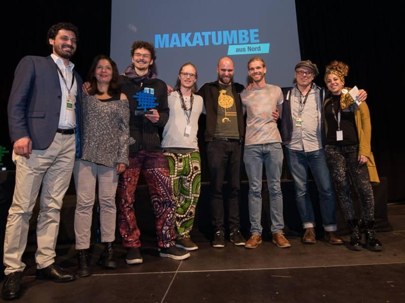 Die Preisträger stehen auf der Bühne für ein Gruppenfoto.