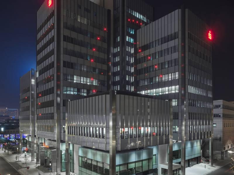 Mehrgeschossiges Gebäude, an dessen Fassade rote Lichtpunkte einen Kreis bilden.