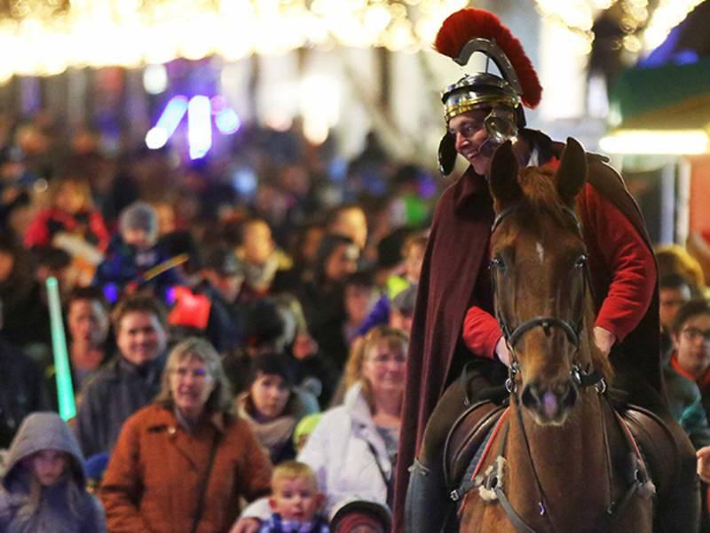 Ein Mann reitet als St. Martin verkleidet hinter einem Fanfarencorps.