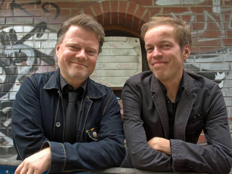 Zwei lachende Männer in dunklen Jacken vor einer Steinmauer.