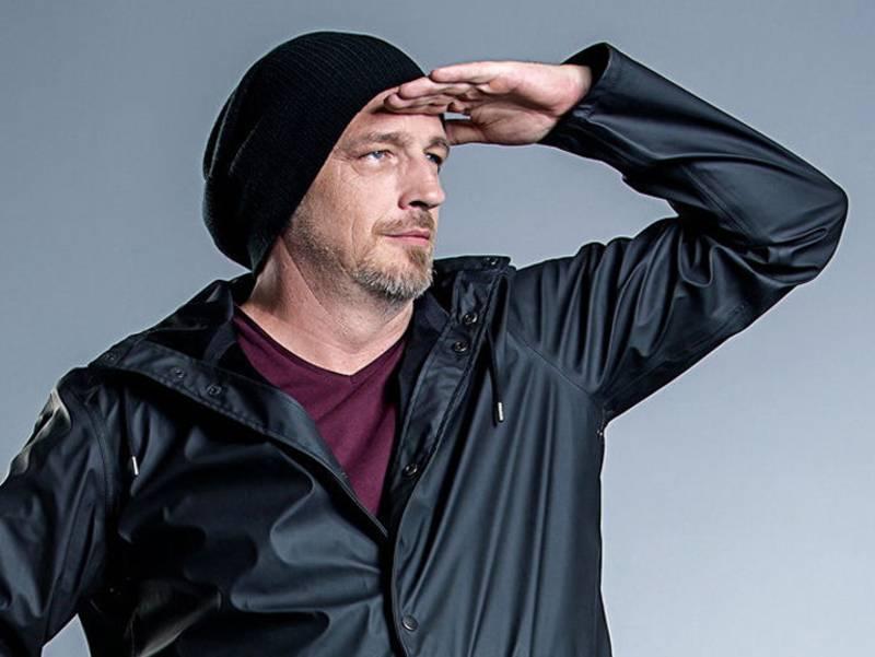 Ein Mann mit schwarzer Jacke und Mütze hält sich in ausschauhaltender Geste eine Hand vor die Stirn.