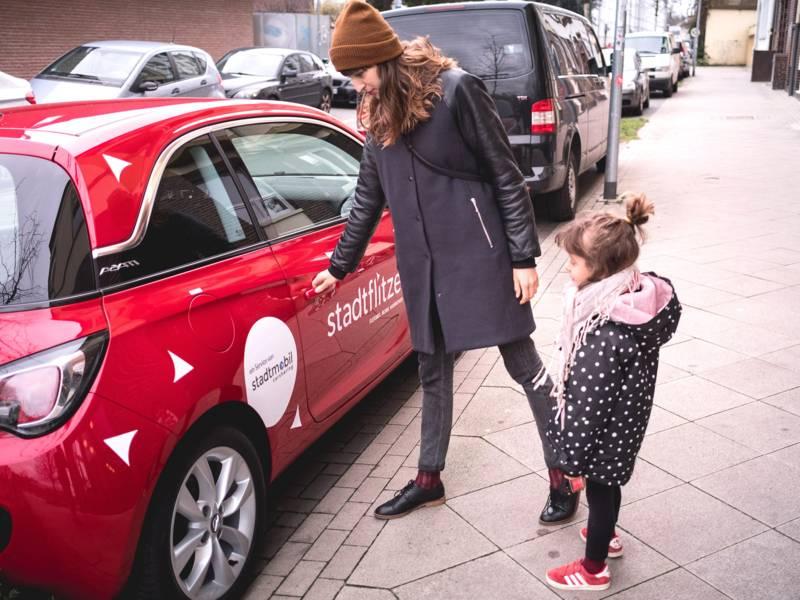 """Frau und Kind vor Auto mit der Aufschrift """"Stadtflitzer"""""""