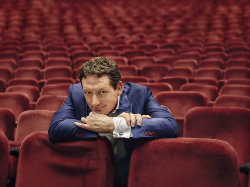 Ein Mann mit blauem Anzug lehnt einem leeren Theatersaal auf den roten Samtsitzen.