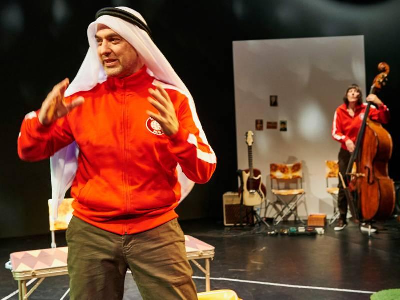 Ein Mann mit Jacke und arabischen Kopftuch, im Hintergrund eine Frau mit Cello und gleicher Sportjacke.
