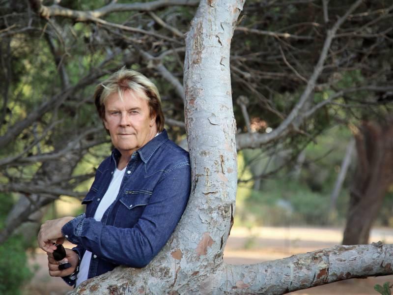Ein älterer Mann lehnt an einem Baum.