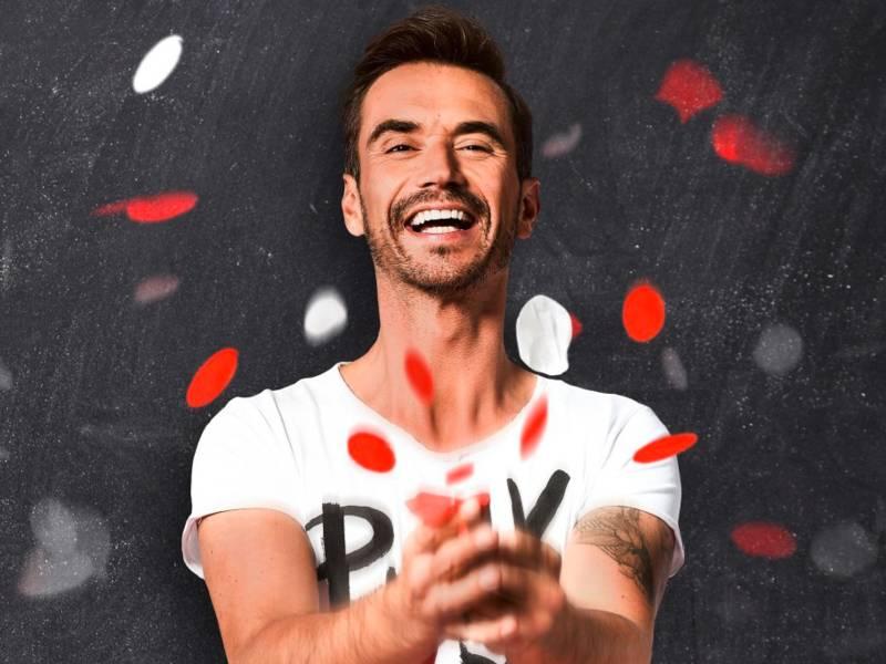 Ein Mann wirft rot-weißes Konfetti in die Luft.