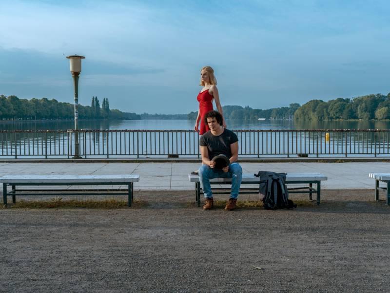 Ein Mann sitzt an einem Stadtsee auf einer Bank, darauf steht eine Frau in rotem Kleid.