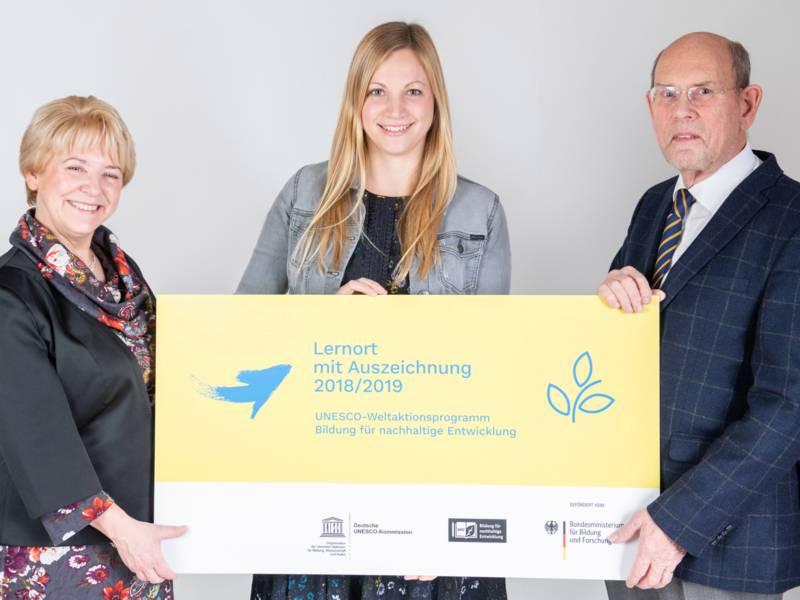 """Drei Personen halten ein Schild in der Hand, mit der Aufschrift """"Lernort mit Auszeichnung 2018/19"""""""