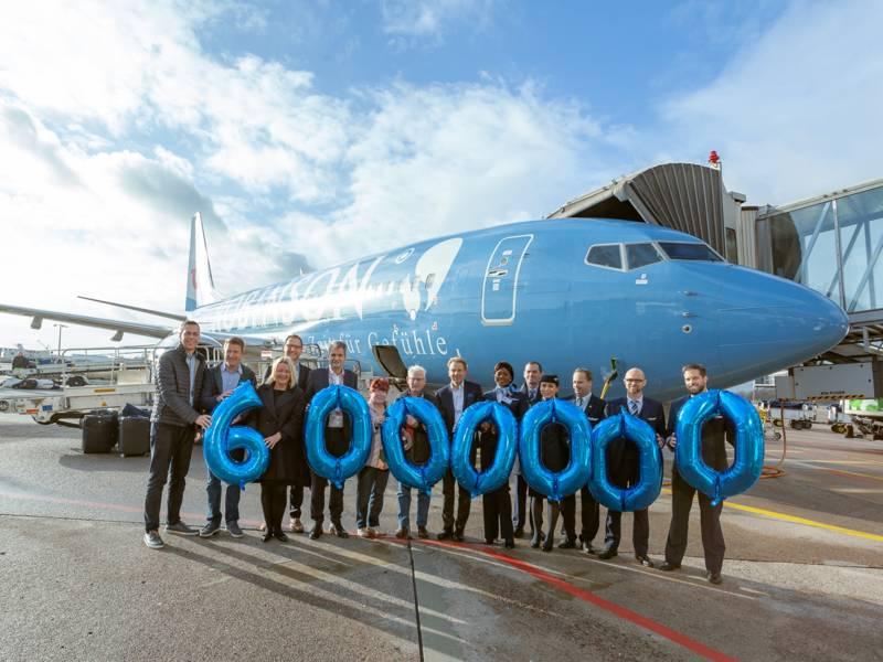Menschen vor einem Flugzeug, die Ballons halten, die die Zahl Sechsmillionen darstellen.