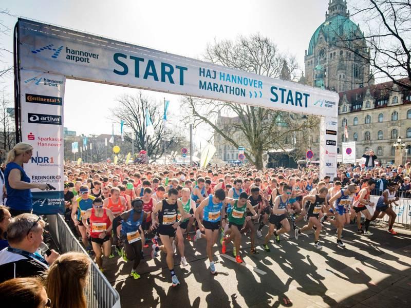 Hunderte von Läufern laufen unter einer Start-Markierung hindurch.