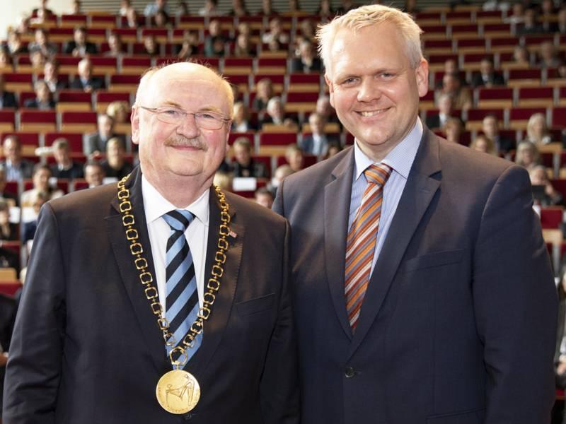 Zwei Männer, einer trägt eine goldene Kette um den Halt