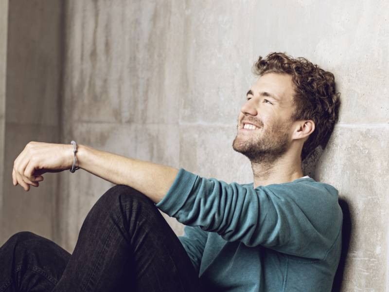Mann sitzt lächelnd an Wand gelehnt