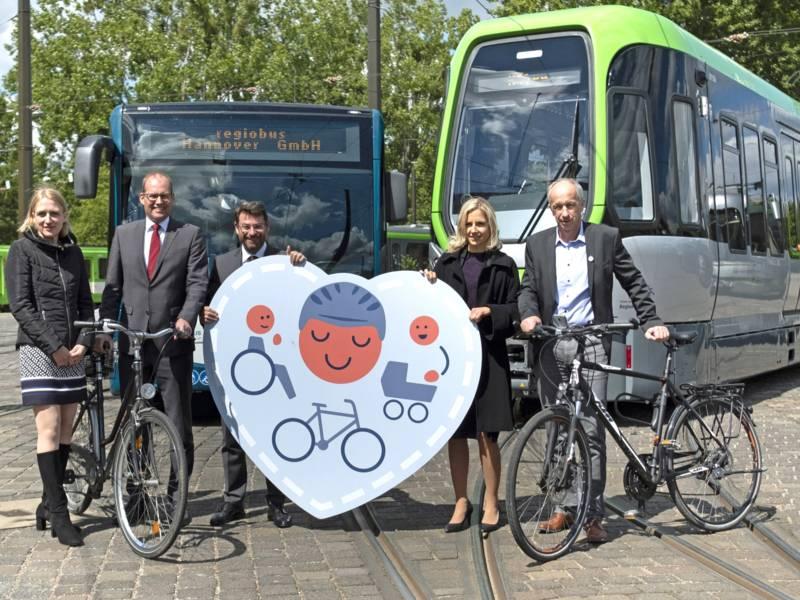 Fünf Personen mit Fahrrädern vor einem Bus und einer Stadtbahn