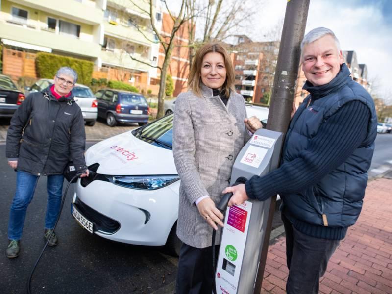 Zwei Frauen und ein Mann an einer Straßenlaterne mit einer Aufladeanlage für Elektroautos
