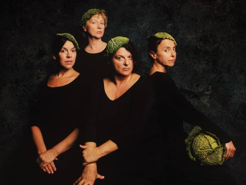 Vier Frauen mit je einem Salatblatt auf dem Kopf