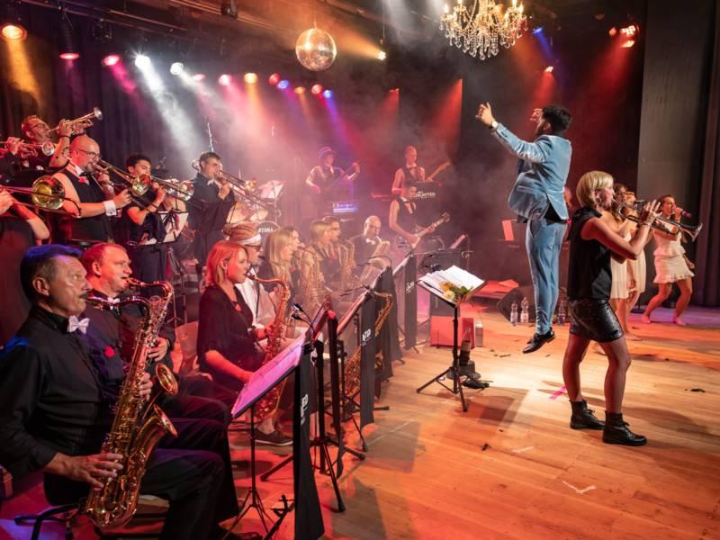 Viele Musiker spielen auf der Bühne ihre Instrumente