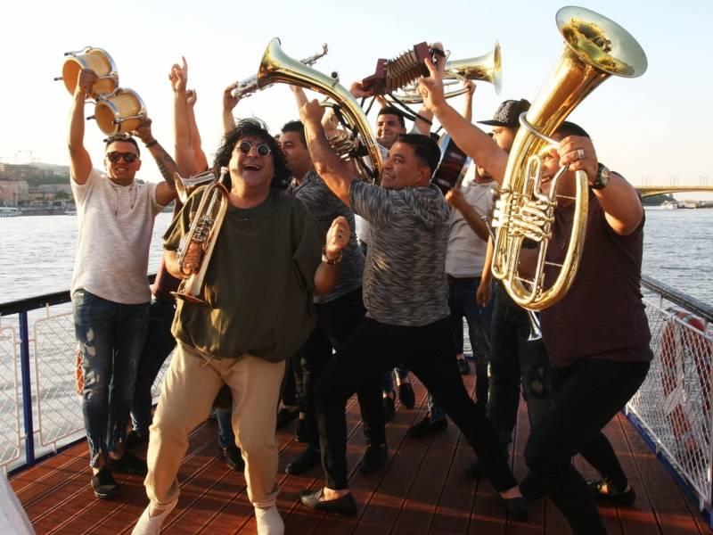 Viele Menschen mit Musikinstrumenten stehen auf einem Steg