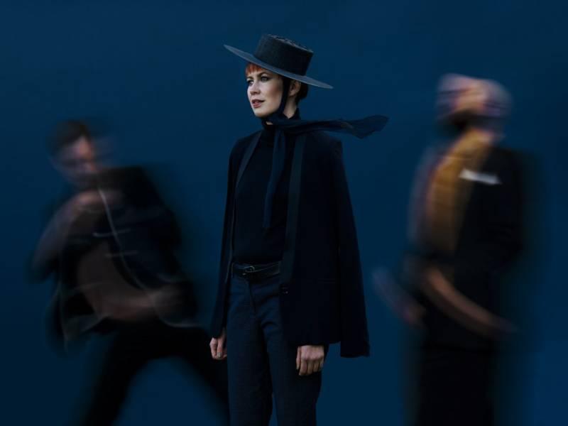 Eine Frau vor dunklem Hintergrund, mit Hut und dunkler Kleidung