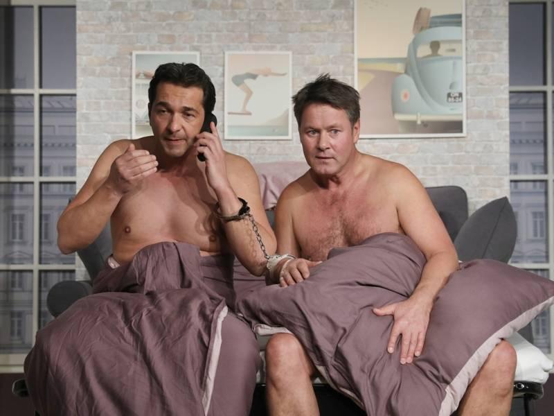 Zwei nackte Männer sitzen nebeneinander im Bett. Der eine telefoniert.