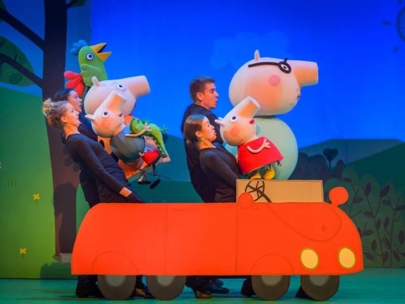 Personen, komplett in schwarz gekleidet halten jewils eine der Peppa Pig Puppen in der Hand. Sie befinden sich in einem roten Papp- Auto.