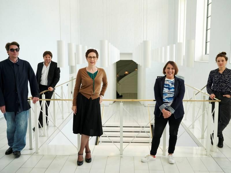 Zwei Männer und drei Frauen stehen versetzt in einem Treppenhaus.