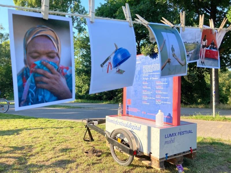 Fahrrad mit Anhänger vor Leine, an der Fotos hängen
