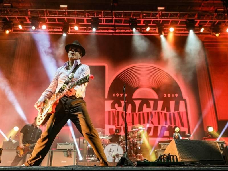 Ein Mann mit Hut und Gitarre steht auf einer rot-beleuchteten Bühne.