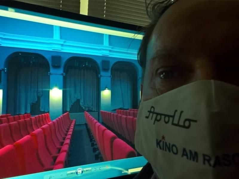 Mann vor Bildschirm, auf dem ein Kinosaal zu sehen ist.