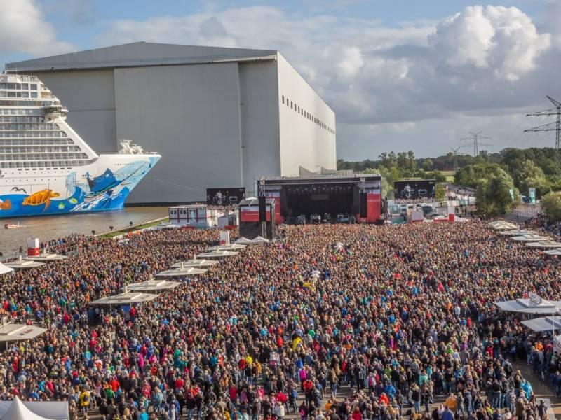 Eine große Menschenmenge steht vor einer Bühne. Links ist ein Kreuzfahrtschiff und es gibt viele Getränk- und Essensstände.
