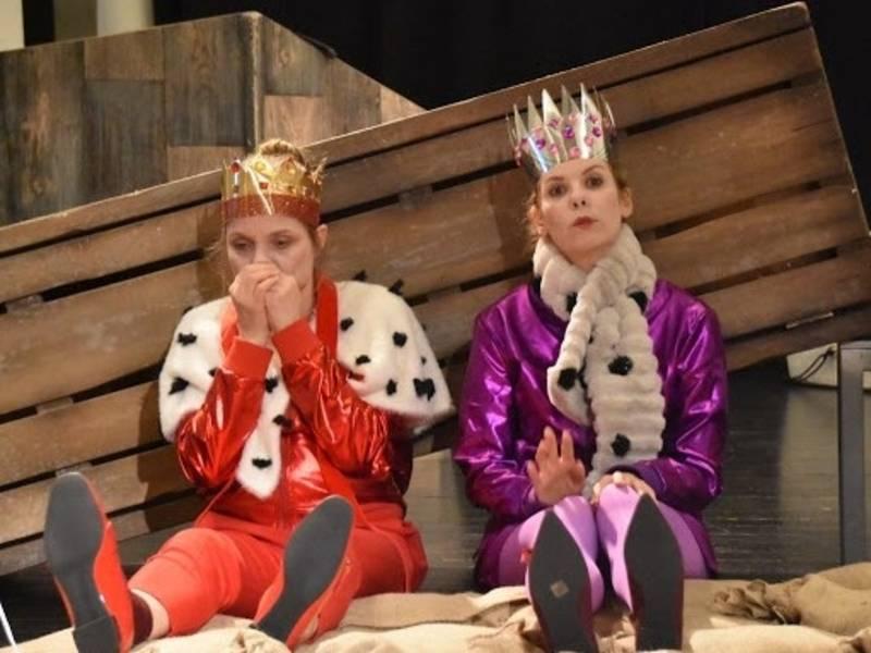 Zwei Frauen in Königskostümen sitzen auf dem Boden. Das eine Kostüm ist rot, das andere lila. Sie tragen beide Kronen.
