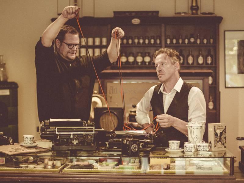 Zwei Männer in einem Raum mit altem Mobiliar und antiken Schreibmaschinen