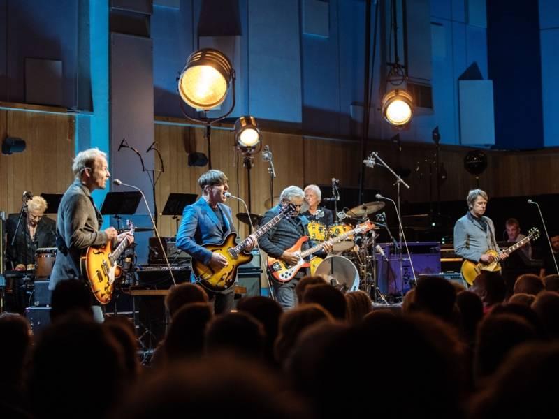 Ein paar Männer stehen auf einer Bühne und singen.