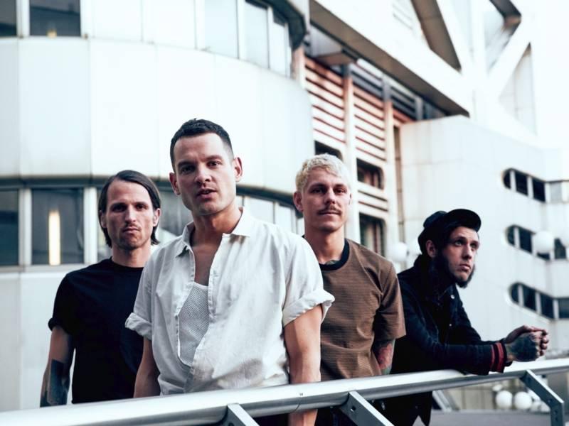 Vier Männer stehen verstetzt vor einem hellen Hintergrund. Drei der Männer haben recht große Armtattoos. Alle tragen T-Shirts und nur drei schauen direkt in die Kamera.