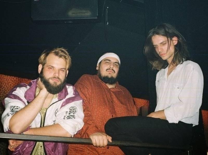 Drei Männer sitzen in einem dunklen Raum. Der eine Mann hat lange Harre und trägt ein weißes Hemd. Der Mann in der Mitte trägt ein weißes Stirnband und ein orangenes Hemd und hat einen Vollbart. Der Mann links hat blond gefärbte Harre und einen langen Vollbart. Er trägt eine bunte Jacke.